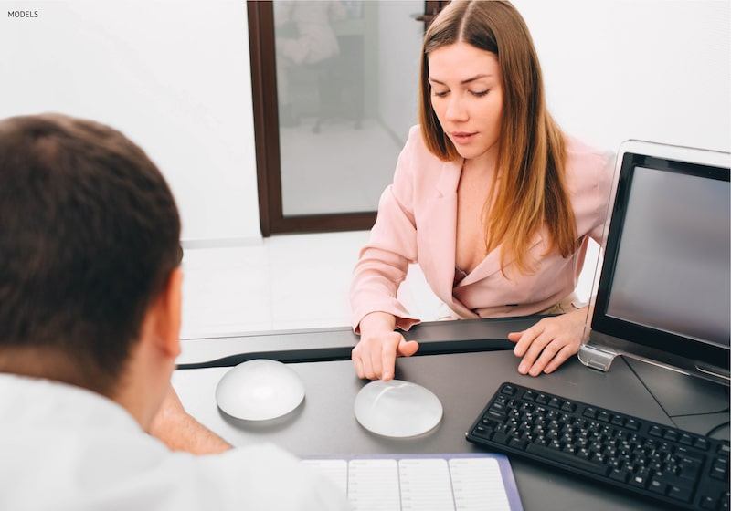 A woman picking out a silicone breast implant after seeing a Vectra simulation.