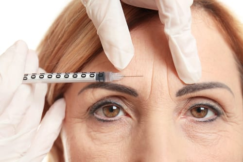 Woman Receiving Injection into Glabellar Lines